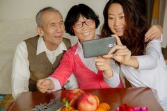 Daughter and senior parents using smartphone at home. royalty free stock images