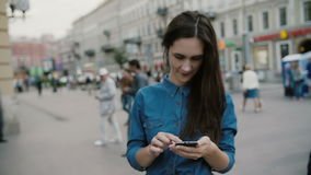 Modern technology. Beautiful brunette young woman in a denim dress using her smartphone in a busy street. Slow mo