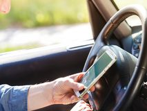 Man using his phone while driving car. Royalty Free Stock Photography