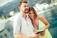 Modern technology devices and tourism concept. Young couple outdoor against sea boats with tablet enjoying summer holidays stock photos