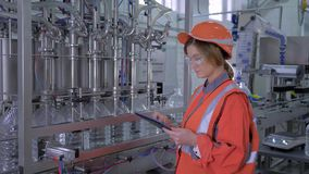 Modern technology at factory, industry worker female into helmet uses digital tablet to control operation of conveyor stock video