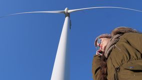 Modern technology, female in sunglasses talking on mobile phone standing under windmill against blue sky. Modern technology, female in sunglasses talking on stock video