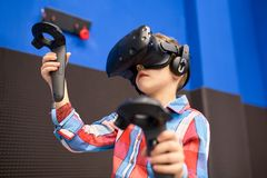 Modern technology, gaming and people concept - boy in virtual reality headset or 3d glasses playing videogame at game. Modern technology, gaming and people stock photo