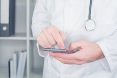Modern technology in healthcare and medicine. Male doctor using smartphone in office Royalty Free Stock Photography
