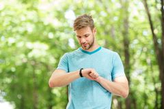 Modern technology. Wrist band gadget. Athlete check fitness tracker nature background. Athlete with bristle looks at. Pedometer gadget progress result stock photos