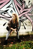 Modern Teen by Graffiti Wall. Contemporary teenage girl leaning against an exterior wall covered by graffiti art.  Grunge concept Stock Photography