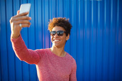 Modern teenage guy taking a self portrait over colorful background. Closeup outdoors shot of young hipster man taking a selfie with smart phone by a blue wall Stock Photos