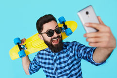Modern teenage guy taking a self portrait over colorful background. Closeup studio shot of young hipster man taking a selfie with smart phone by a blue wall Stock Images