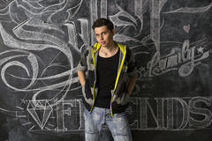 Modern teenager in front of blackboard. High contrast portrait of modern teenager in front of blackboard Stock Photo
