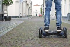 Modern teknologi, en man rider på en svart tavla Slut upp av dubbelhjulsjälven som balanserar den elektriska skateboarden Smart p royaltyfri foto