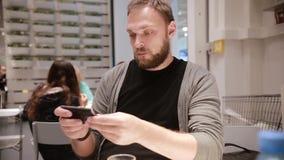 Modern teknologi i ett offentligt ställe Stilig ung man med ett skägg genom att använda hans smartphone stock video
