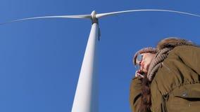 Modern teknologi, kvinnlig i solglasögon som talar på mobiltelefonanseende under väderkvarnen mot blå himmel stock video