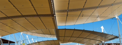 Modern Tensile Structure on Blue Sky. Detail of a modern tensile structure, membrane fabric roof with poles and steel cables, on a blue clear sky Stock Images