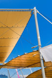 Modern Tensile Structure on Blue Sky. Detail of a modern tensile structure, membrane fabric roof with poles and steel cables, on a blue clear sky Royalty Free Stock Image
