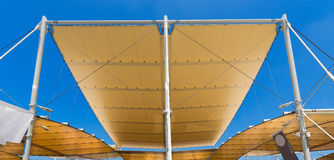 Modern Tensile Structure on Blue Sky. Detail of a modern tensile structure, membrane fabric roof with poles and steel cables, on a blue clear sky Stock Photo