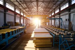 Modern thermal insulation sandwich panel production line. Machine tools, roller conveyor and overhead crane in workshop.  stock photography