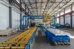 Modern thermal insulation sandwich panel production line. Machine tools, roller conveyor and overhead crane in workshop.  stock photos