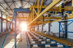 Modern thermal insulation sandwich panel production line. Machine tools, roller conveyor and overhead crane in workshop.  stock image