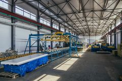 Modern thermal insulation sandwich panel production line. Machine tools, roller conveyor in workshop.  stock image