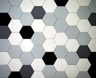Modern tiled floor with hexagonal tiles. Colors are black,white, light and dark gray randomly arranged.  stock photography