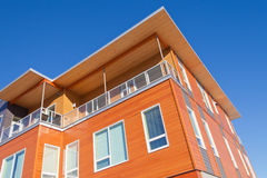 Modern timber clad condo building exterior detail. Upper storey detail of timber clad apartment building painted bright with penthouse balcony under blue sky Royalty Free Stock Photos