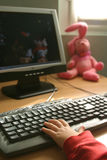 Modern times. Child's hand on a keyboard with an old toy on the side Stock Photo