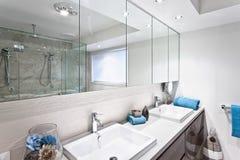 Modern toalett med vattenkranar och breda speglar Royaltyfri Bild