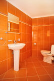 Modern Toilet Interior. Exciting modern bathroom with orange wall paper Stock Images
