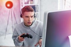 Modern tonåringkänsla som förbluffar, medan spela hans favorit- dataspel fotografering för bildbyråer