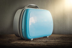 Modern tourist luggage on wooden tabletop against grunge wall Royalty Free Stock Photography