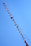 Modern tower crane against blue sky. Royalty Free Stock Image