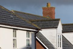 Modern town house roof with slate tiles, chimney and white dorme Royalty Free Stock Images