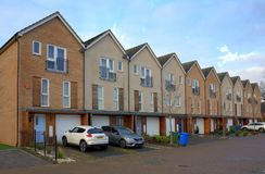 Modern Town Houses on a housing estate in Bracknell, England. Bracknell,England - January 22, 2018: Row of modern Town Houses with Garages underneath and cars Royalty Free Stock Image