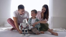 Modern toys, little boy with mother and father plays Humanoid robot on remote control of smartphone sitting on floor. At room