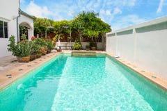 Modern trädgård av en simbassäng med huset arkivbilder