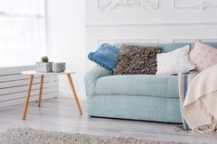 Modern träkaffetabell och slags tvåsittssoffasoffa med kuddar Vardagsruminre och enkelt modernt hem- dekorbegrepp arkivfoton