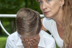 Modern tröstar den upprivna sonen Arkivbilder