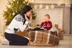 Modern tröstar hennes lilla skriande son på bakgrund av julgranen royaltyfria bilder