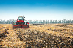 Modern tractor in the field with complex for the plowing. Royalty Free Stock Photo