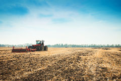 Modern tractor in the field with complex for the plowing. Royalty Free Stock Photos