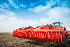 Modern tractor in the field with complex for the plowing of soil. Stock Photo