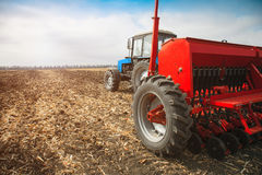 Modern tractor in the field with sowing complex. Royalty Free Stock Images