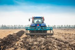 Modern tractor in the field on a sunny day. Royalty Free Stock Photo
