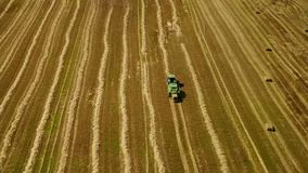 Modern tractor makes haystacks on the field after harvesting. Aerial motion view stock video footage