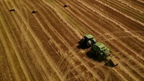 Modern tractor makes haystacks on the field after harvesting. Aerial motion view stock footage
