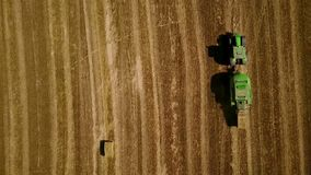 Modern tractor makes haystacks on the field after harvesting. Aerial top motion view stock footage