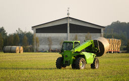 Modern tractor moving hay bales Stock Image