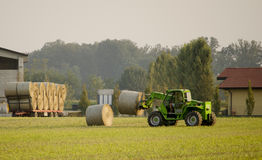 Modern tractor moving hay bales stock photos