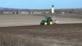 Modern tractor ploughing rough land on agricultural field before sowing seeds. Kamchatka Peninsula, Russia - 29 May, 2018: Modern tractor John Deere ploughing stock video footage