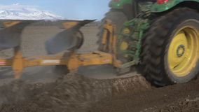 Modern tractor ploughing rough land on farming field. Farm work on sunny weather. Kamchatka Peninsula, Russia - 29 May, 2018: Yellow-green modern tractor John stock video